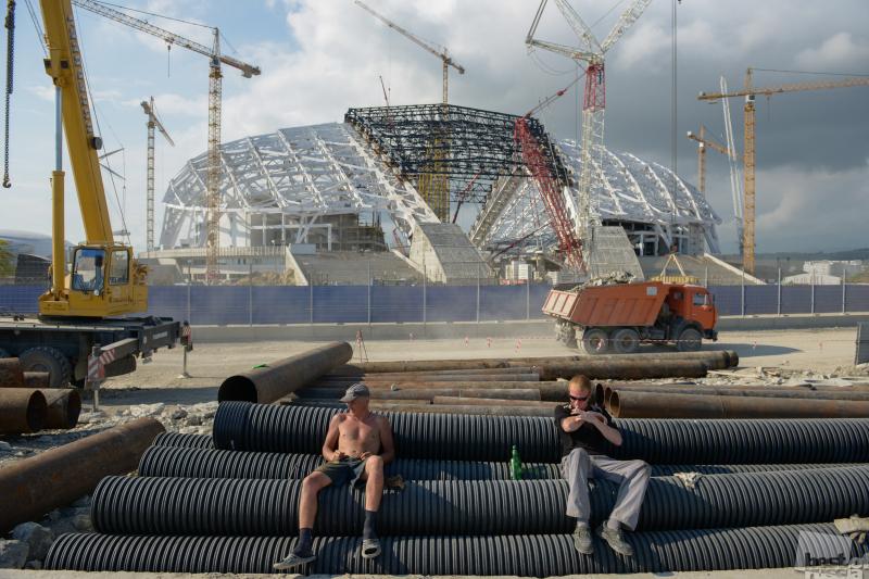 """Рабочие отдыхают на фоне строящегося Олимпийского стадиона """"Фишт"""""""