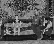Дедушка играет на гармони для внука