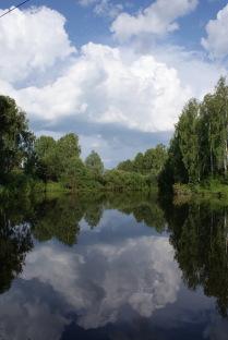 В реку смотрятся облака.