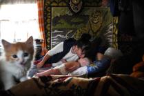Мама с ребенком и котенок на фоне ковра с тигром.
