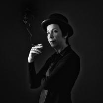 Портрет курящей женщины в шляпе.
