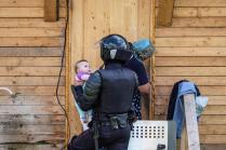Сотрудник ОМОН с ребенком во время сноса незаконных построек в цыганском поселке в Плеханово Тульской области